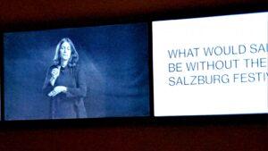 """Das Bild zeigt eine Projektion in einer Ausstellung. Eine Dame gebärdet und die Wörter """"Was wäre Salzburg ohne die Salzburger Festspiele?"""""""