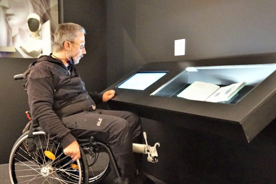 Ein Mann im Rollstuhl schaut in eine Museumsvitrine mit einem Buch ein.