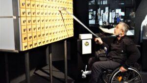 Ein Mann im Rollstuhl öffnet eine Schublade außer seiner Reichweite mit einer Greifzange